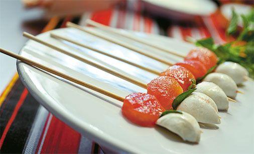 Espetinhos caprese da Ghee Banqueteria unem bolinhas de mussarela, uma folha de manjericão fresco e tomates-cereja sem pele temperados com sal e um fio de azeite