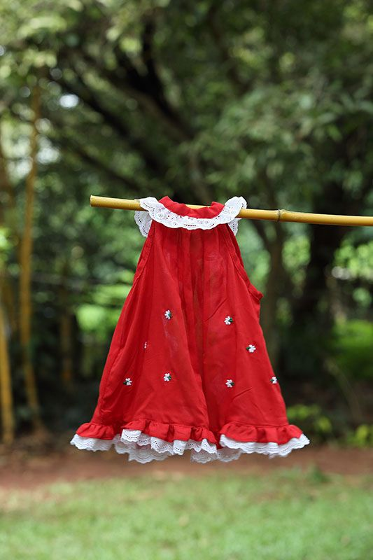 Elegant red cotton finish red fabric frock with lace trim . The white and red combo looks so in synch with the Christmas festive season.