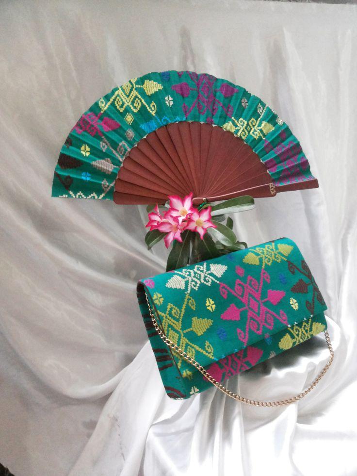 Clutch terbuat dari bahan Songket Bali, dalaman sued yang dilengkapi dengan satu kantong memanjang di dalam, rantai warna gold 60 cm. Kipas 25 cm, stick kayu lokal Bali.