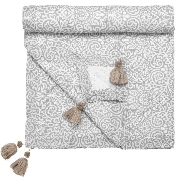 Lekkert teppe i vattert bomull, med dusker i hjørnene. Lysegrått og hvitt, fint som pledd og som sengeoverkast. 140x200cm stort.