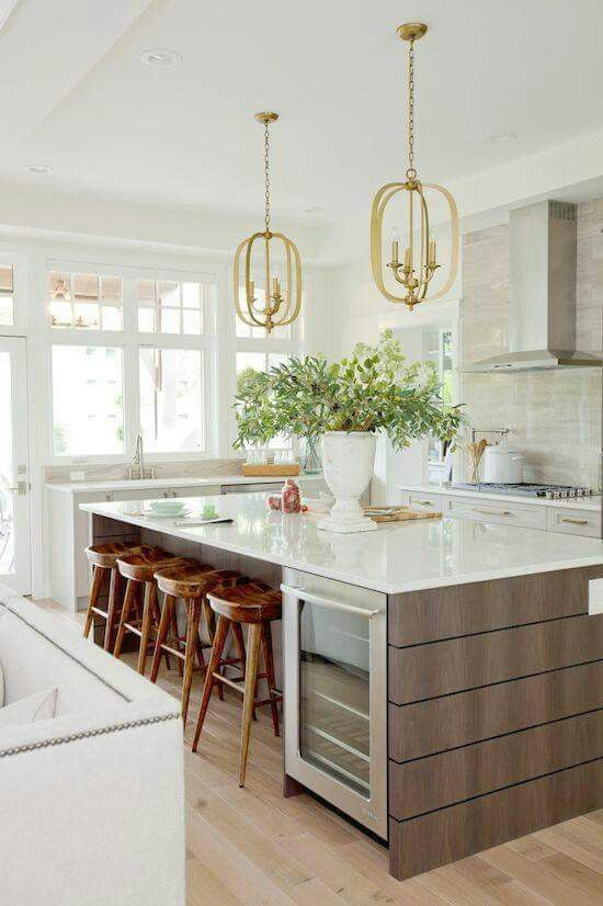 Love the look of the gold pendants + warm wood stools in this modern kitchen space.