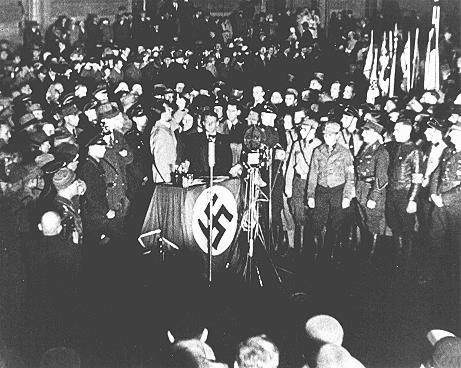 """O Ministro da Propaganda Joseph Goebbels (no palanque) enaltecendo os estudantes e membros das <i>Sturm Abteilung</i>, Tropas de Choque nazistas, por seus esforços para destruir trabalhos considerados """"não-alemães"""", durante a noite de queima dos livros na Praça da Opera em Berlim, Alemanha. Dia 10 de maio de 1933."""