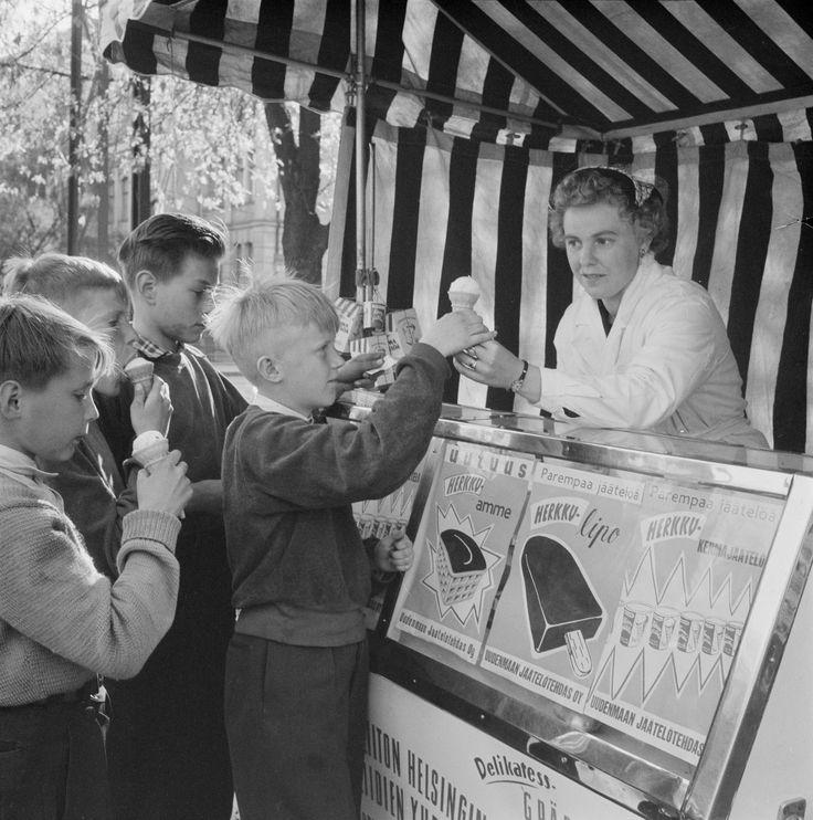 Kevät on tuonut katukuvaan jäätelökioskit ja jäätelöä ostavat pikku pojat. Kuhinaa Uudenmaan Jäätelötehtaan kioskilla keväällä 1956. Helsinki 30.5.1956. Valokuvaaja tuntematon/Suomen valokuvataiteen museo/Alma Media/Uuden Suomen kokoelma