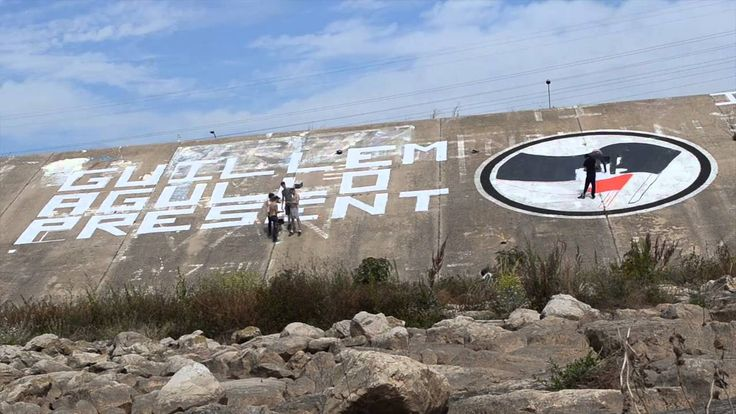 Mural Guillem Agulló present  fet en memòria de Guillem Agulló per membres de la Coordinadora 11 d'Abril i companys d'Acció Antifeixista València https://www.youtube.com/attribution_link?a=AnOA9EBbFYc&u=%2Fwatch%3Fv%3DcPgjZWbHNxE%26feature%3Dshare