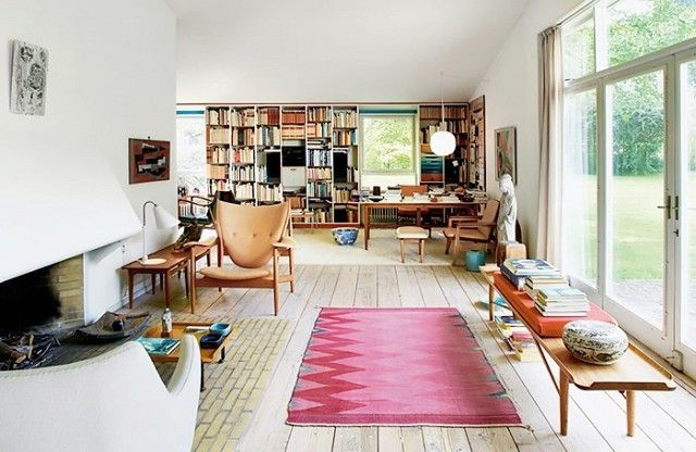 Swedish living space with large windows, wood floors and a chieftain chair