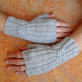 Ribbed fingerless mitts with cables that draw in the wrists.