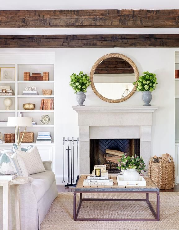 Chic living room features a gray linen sofa lined with blue pillows facing a brickmaker's coffee table placed atop a jute rug.