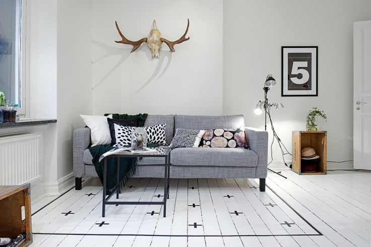Painted rug on a white floor.  From c o z y. I love the vinyl idea on the floor!!!