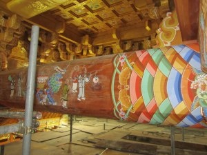 This picture is taken by Chong Go Sunim, and his dharma brothers have been working on building this Dharma  Hall. This artwork is painted. The color bands  in this picture represents waves of energ radiating outward into the world from  fundamental Buddha essence. The golden bat in this artwork are known as a dharma protector in Korean Buddhism.