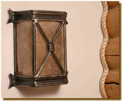 """Rustic yet contemporary, this sconce is made of decorative metal that crosses in the front and is decorated with iron rings. Silver or gold mica available as is all finishes. This light is UL listed to hold two 60 watt bulbs. 12"""" Wide 5"""" Deep 12"""" Deep."""