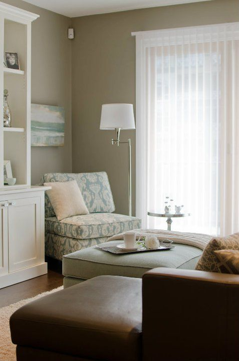 Color palette for basement - taupe walls, blue paisley accent chair, white media cabinet blue velvet ottoman with white piping, brown leather sectional sofa