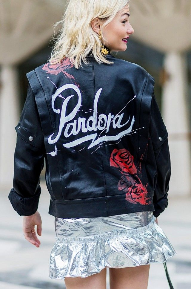 Pandora Sykes wears a paint splattered personalized leather jacket, metallic mini skirt, and gold drop earrings.