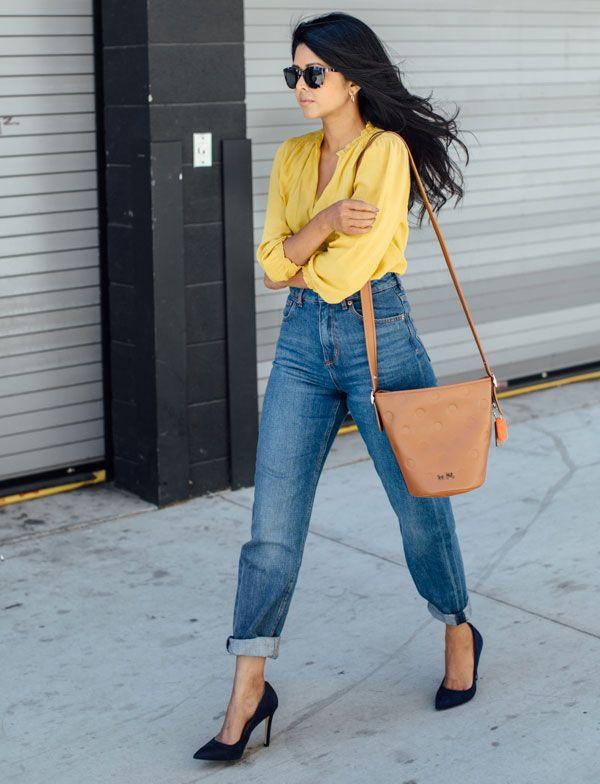 Look street style com calça jeans + camisa amarela + scarpin preto.