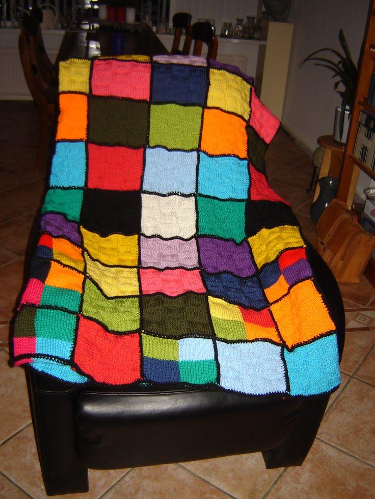 Een glas-in-lood deken, gebreide lapjes van 30 steken en 36 naalden, in verschillende kleuren acrylgaren (wibra-zeeman), van elke kleur 5, afgewisseld met lapjes met blokken van 4 kleuren. Aan elkaar vastgehaakt met vasten in zwarte acryl, afgewerkt met rondom een toer vasten en een toer kreeftensteek (=vaste, maar dan van links naar rechts gehaakt, de steek kruist zich dan).