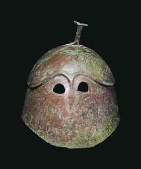 A GREEK BRONZE PSEUDO-CORINTHIAN HELMET -  MAGNA GRAECIA, CLASSICAL PERIOD, CIRCA 5TH CENTURY B.C. 8 ½ in. (21.6 cm.) high
