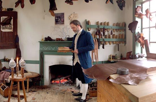 """Today, the shoemaker's shop in Williamsburg represents the firm of George Wilson, who moved to Williamsburg from Norfolk, Virginia in the late 1760s. In 1773, George Wilson specialized in """"Boots & Shoes for Gentlemen,"""" which he boldly advertised in the Virginia Gazette. Boot making was the most sophisticated & prestigious branch of the trade. Following a centuries-old tradition, the making of boots & shoes for men & the making of shoes for women were separate pursuits."""