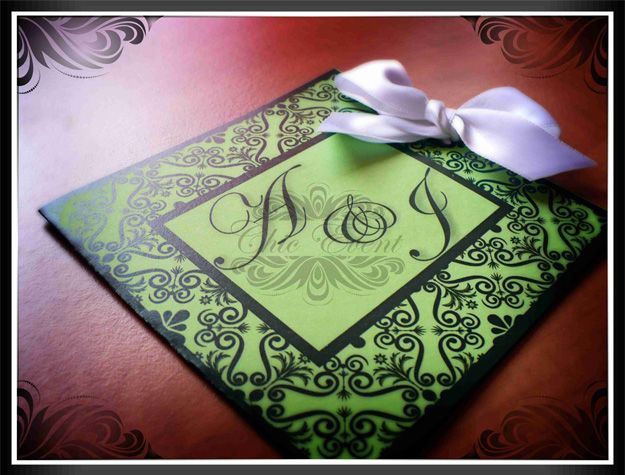Wedding invitation card on colored cardboard with colored ribbons.