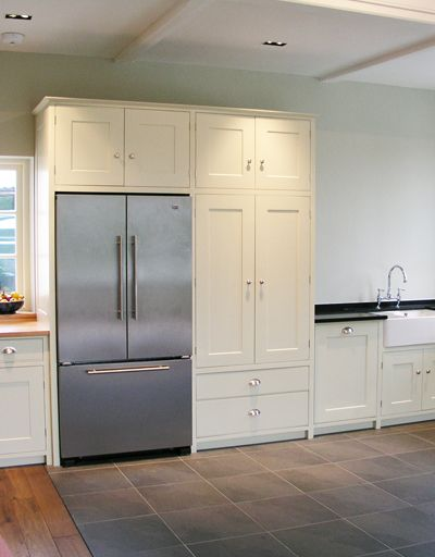 Hand painted bespoke cupboards with  honed granite and our own bespoke English oak worktops. Integrated American fridge/freezer and adjacent pantry cupboards