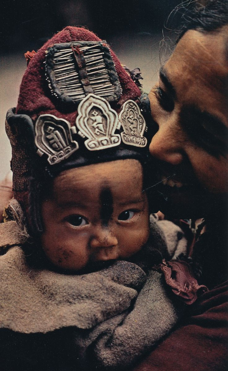 """The woolen cap on a younger child guards against cold winds, while the amulets and needles that decorate it war doff evil spirits."" - National Geographic, 1978, photographed by Thomas J. Abercrombie"