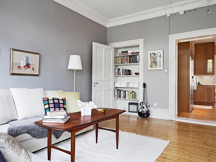 Grey walls warm floors and a book shelf inside an unused door frame