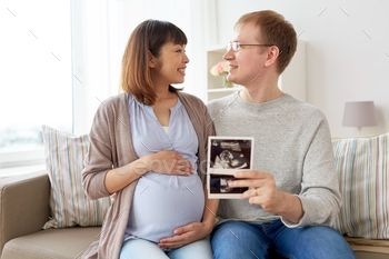 happy couple with ultrasound images at home