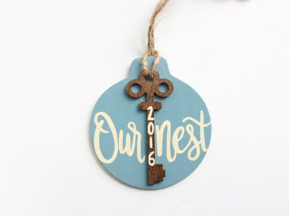 This unique ornament is perfect to celebrate a new home. Makes a great housewarming or newlywed gift!  This ornament is a round wood cut out that measures 3 1/2x4. Its been hand painted a beautiful slate blue. A wooden key cut out has been stained a light brown and glued onto the round cut out. The words Our Nest along with the year have been painted on in a beige color. It has been sanded and distressed for a rustic look. A piece of twine has been attached for hanging.  The back has been…