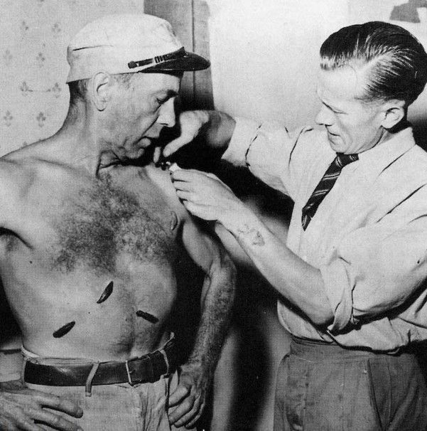 John Juston putting rubber leaches on Humphrey Bogart during the filming of The African Queen.