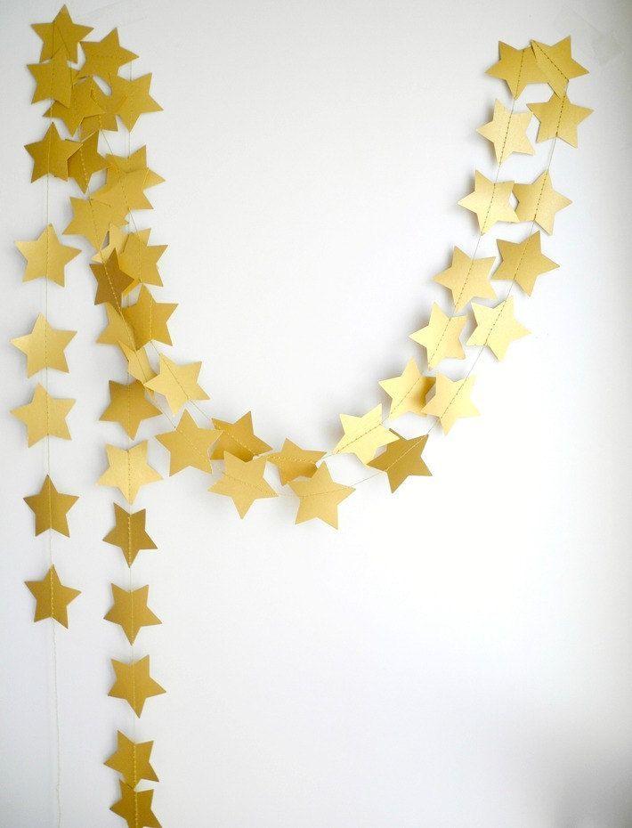 Estrelinhas douradas de papel para decorar a parede de fundo.