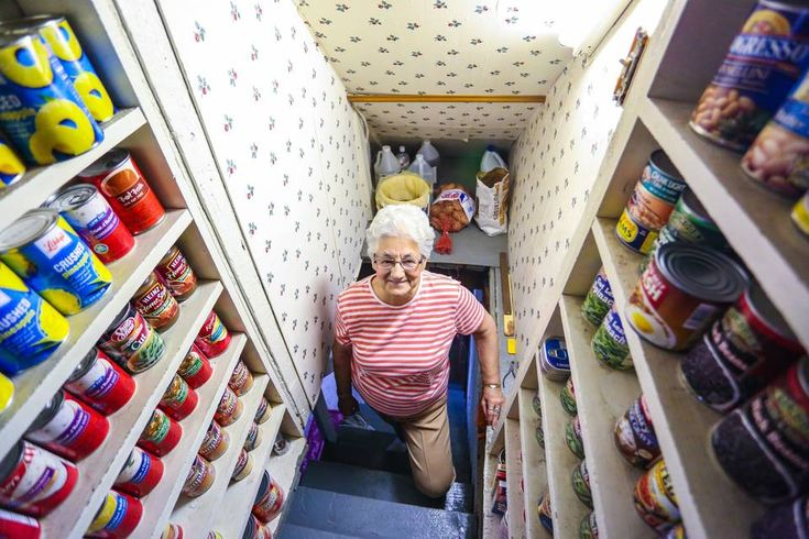 Aldea Campbell, 82, who lives alone in her 102-year-old house in Stockholm, Maine, descends narrow...