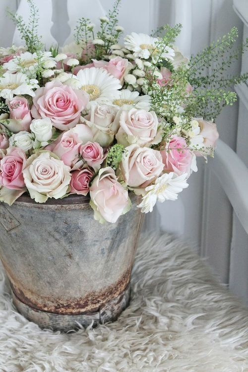 Love the shabby chicness of the pale pink roses, white daisies, and baby's breath in the old galvanized bucket.