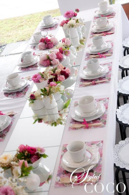 Love this table setting for a tea party. The mirror tiles down the middle adds a certain glamour to the table. They put paper doilies on the stools and doilies under the tea cups. Napkin under the saucer. Don't know about the utensils. I'm thinking maybe plastic but I like the way they tied them with the pink bows.