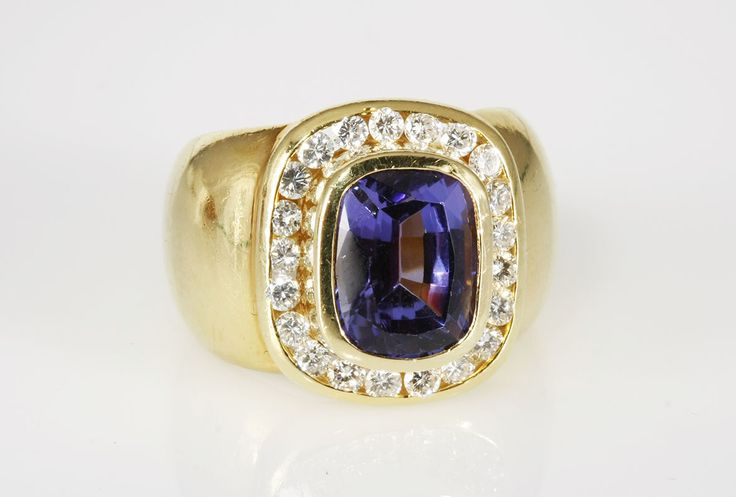 A TANZANITE AND DIAMOND RING, JENNA CLIFFORD,  centred with a bezel-set cushion mixed-cut tanzanite weighing approximately 4,89cts, surrounded by channel-set round brilliant-cut diamonds weighing approximately 0,60cts (G/H VS), in 18ct gold, size K