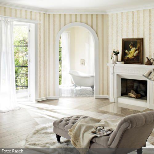 Eine gemütliche Chaiselongue auf einem Fellteppich am Kamin, weiße Gardinen, gestreifte Mustertapeten in Beige und ein Holzboden in einem warmen Holzton schaffen in diesem Wohnzimmer ein richtig romantisches Flair. Ein richtiges Highlight des Wohnzimmers ist das direkt angrenzende Badezimmer mit der freistehenden Badewanne.