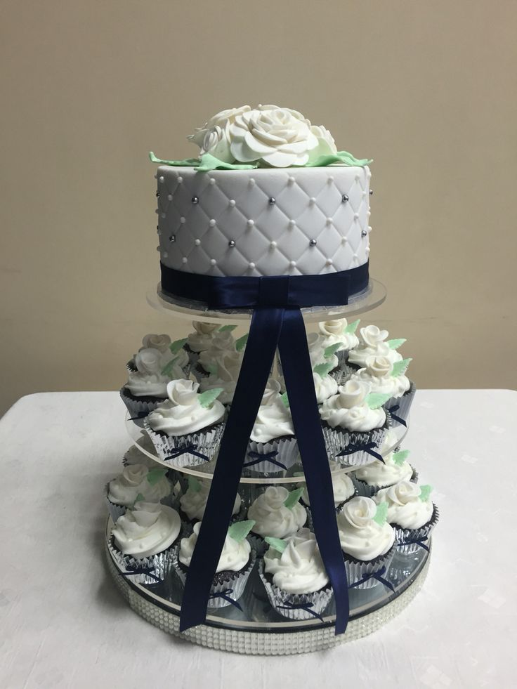 Wedding cake for a friend. Mud cake top tier and cupcakes a mix of mud cake ones and red velvet ones with buttercream vanilla icing and fondant decorations.