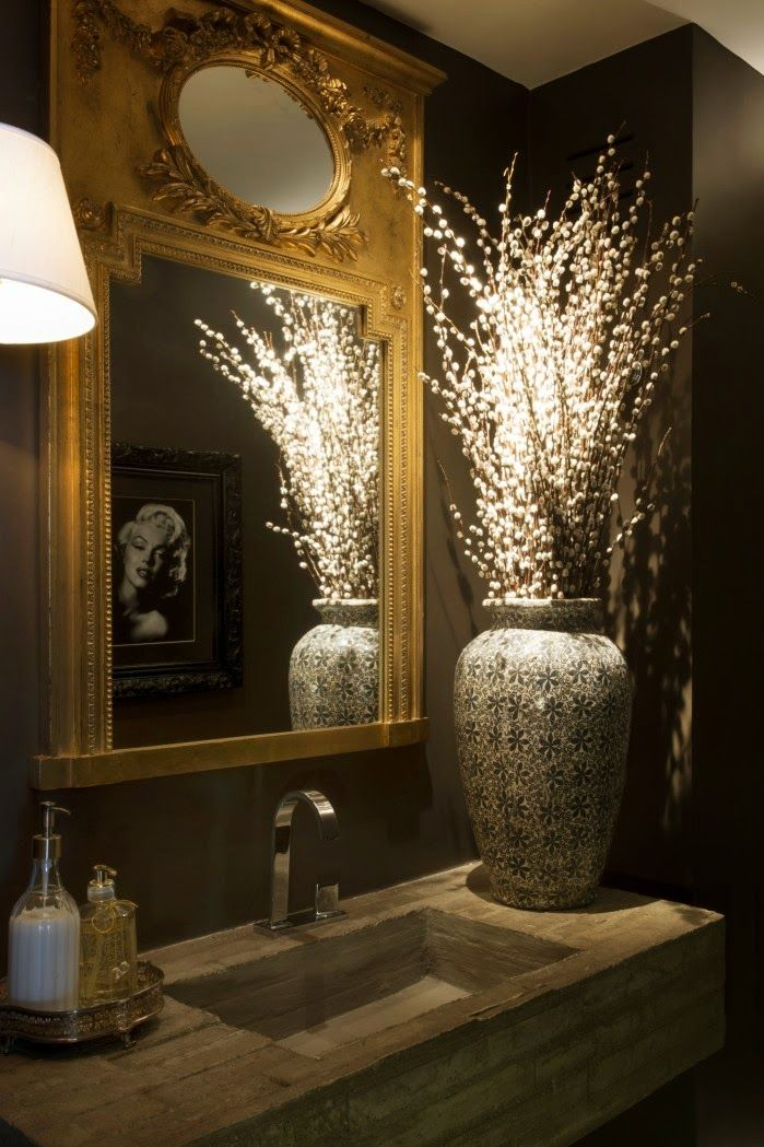very glamorous with the dark colored wall and high contrast gilded french mirror
