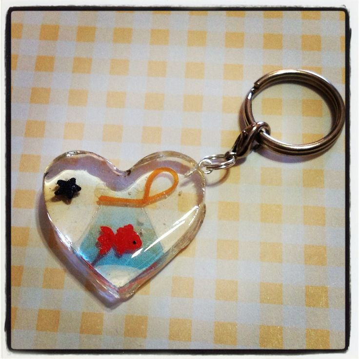 A red koi, or goldfish in a bag, in a heart shaped resin keychain to hang all your keys from! A little black candy star sprinkle is also embedded in the resin, and this keychain is approx. 3cm wide and 3cm in length, and 0.5cm thick.    Given the preserving nature of the resin, the candy sprinkle...