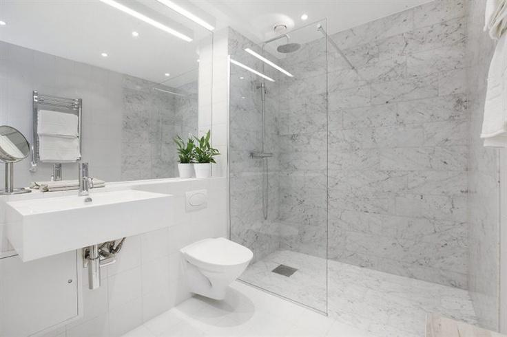 marmorklädd duschdel med glasvägg,