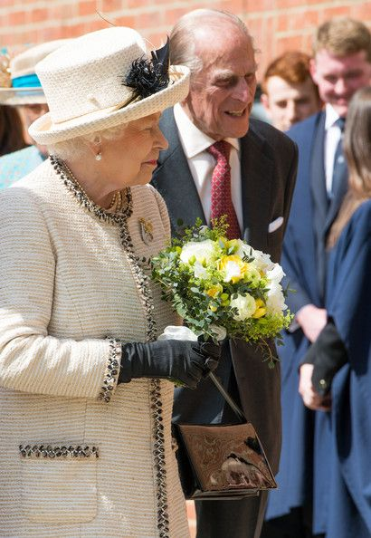 Prince Phillip, Duke of Edinburgh and Queen Elizabeth II receives flowers during an official visit to Felsted School on May 6, 2014 in Felsted, England.