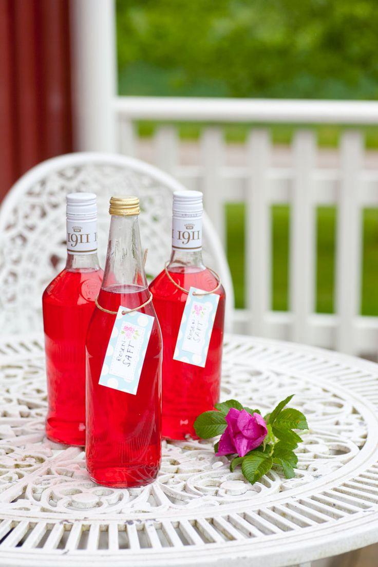 Här hemma har jag en lång vresrosenhäck som ger vackra blommor i rosa. De är inte bara vackra att se på utan även goda att koka saft på. Visst känns det konstigt att koka saft på rosor, men det är det funkar alldeles utmärkt. Och det är dessutom otroligt enkelt och går snabbt. Vad det smakar? Hmm … svårt att beskriva men lite som parfym – fast på ett gott sätt.  När du kokar rosenbladen försvinner färgen men när du tillsätter citronsyran är det som trolleri och den klarröda färgen kommer…