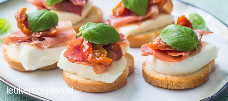 Kleine hapjes om uit te delen met mozzarella, serranoham en tomaat