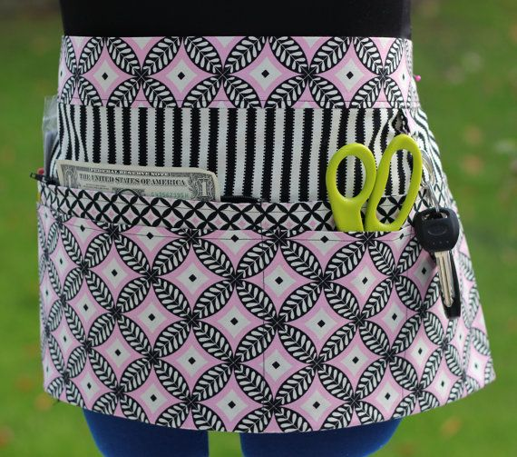 This 8 pocket apron is perfect for carrying everything you need while at a craft show, farmers market, in your studio, kitchen, garden, office, school, or work.    Pink, Black and Creamy White Geometric Pattern with Stripes Pocket Vendor/Craft/Market/Waitress/Utility Apron    The apron is made with 100% cotton designer fabric, featuring a fabulous pink, black and creamy white geometric pattern with a black and creamy white striped background. Very flattering, pretty apron.    8 Pocket Apron…