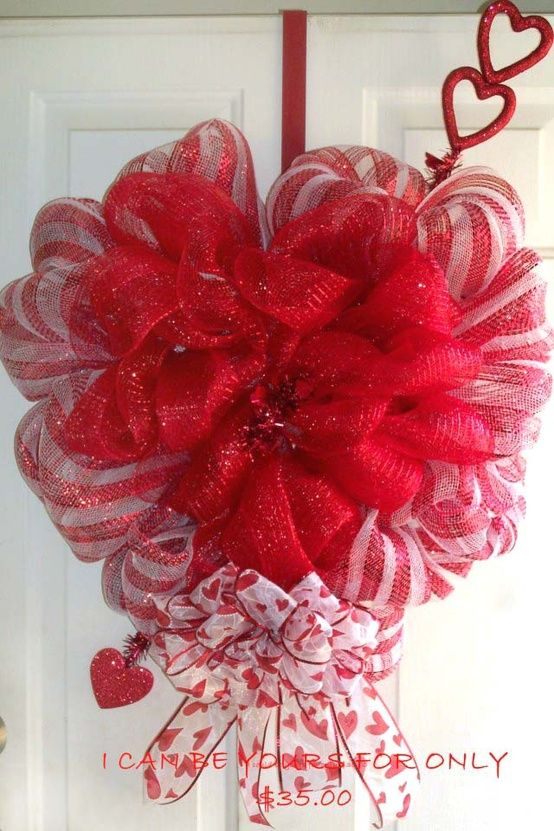 Heart Wreath    Red and white  21″ striped mesh for the outer layer and a 21″ red metallic mesh for the inner layer of her wreath. The wreath was created using a Styrofoam heart. Accent ribbon was sheer white with red hearts. Love the Cupid's arrow!