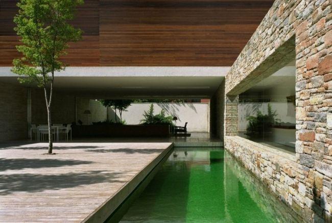 Woda zaprojektowana przy budynku świetnie urozmaica całość projektu i wprowadza naturalny akcent w jego formę. Zestawienie naturalnych materiałów, jak drewno czy kamień, tylko to potęguje. Bo nowoczesne projektowanie to projektowanie naturalne! Zapraszam do posta - Mirindiba House u Pani Dyrektor.