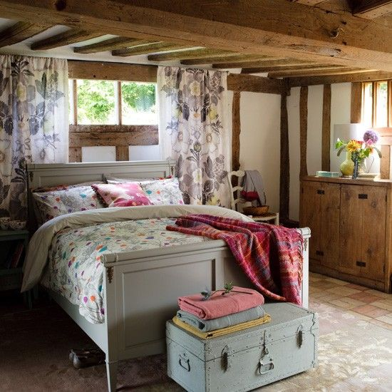 Create a cosy country bedroom with grey painted furniture, soft floral bedlinen and whitewashed walls.