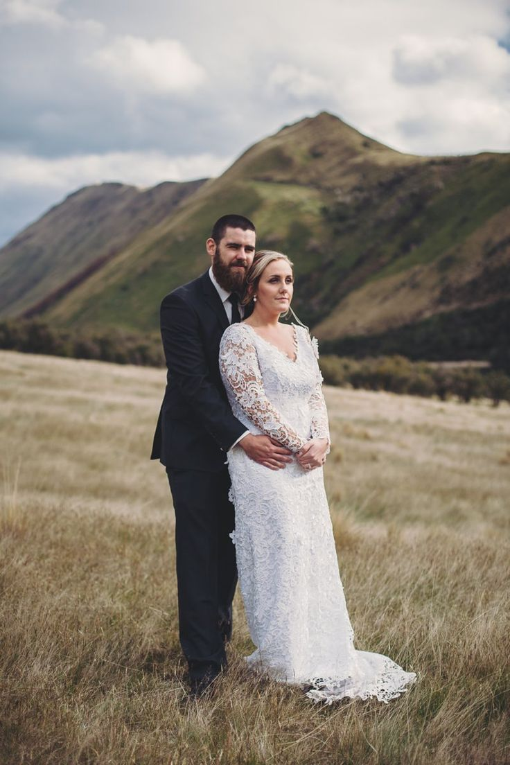 Bride in white lace dress standing lake side at Moke Lake Queenstown Wedding New Zealand. Gown by Nicola Dawson Design.