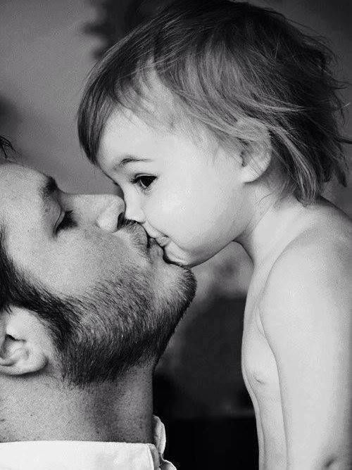 Father kissing baby- black and white