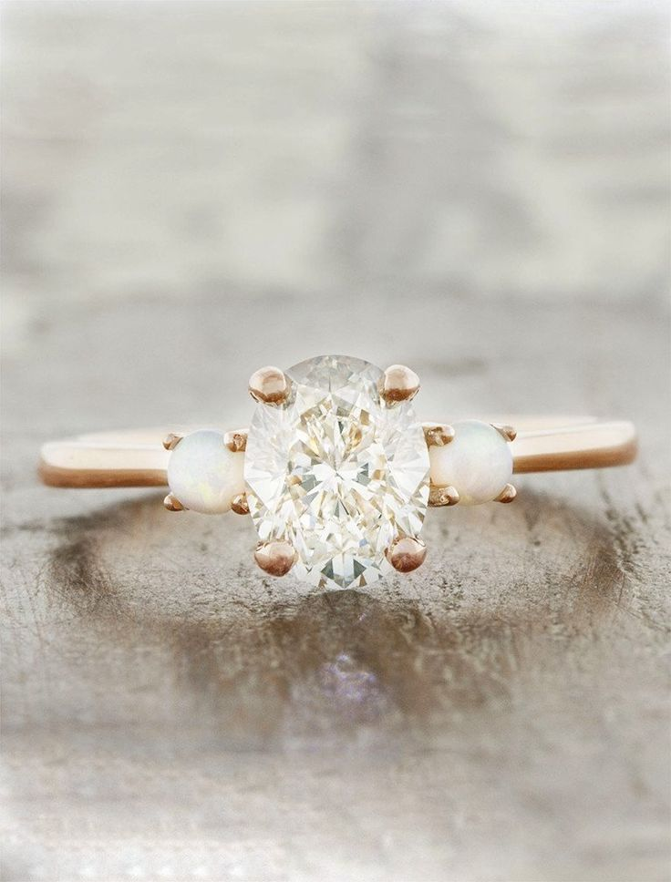 The Percy has a delicate feel, with a soft looking rose gold band and very feminine opal side stones flanking an oval center diamond.