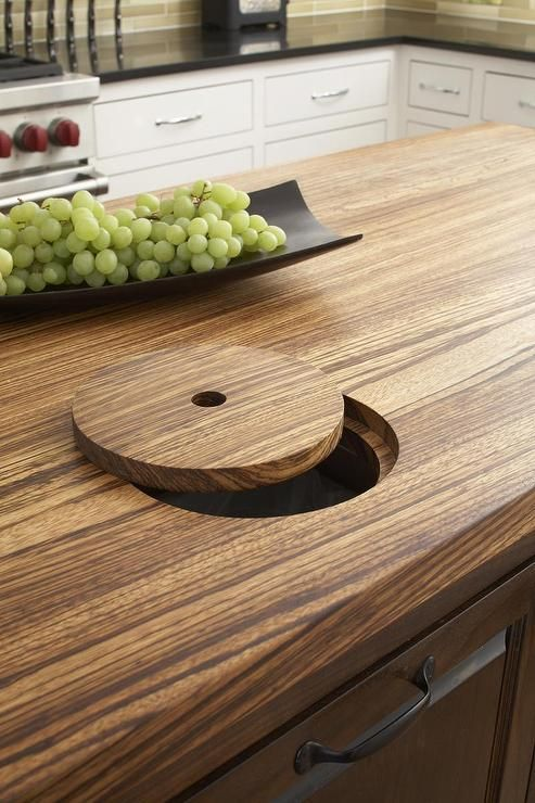 Amazing kitchen features a butcher block island fitted with a trash chute.