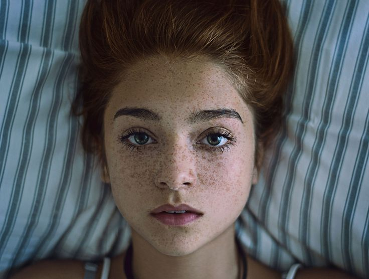 Beautiful portrait of a girl with freckles lying down on a pillow.