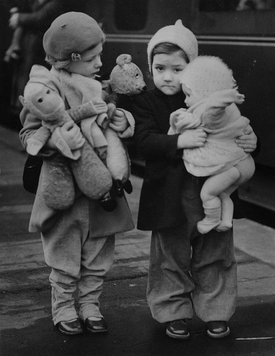 Two little girls clutching their dolls and teddy bears before they leave London for the country on an evacuation train, during the Second World War.
